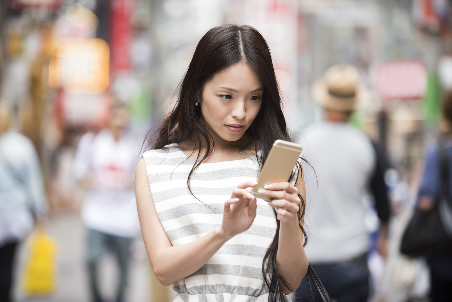 Attractive young Japanese woman using mobile phone to send text message while on the go in urban street in Shibuya, Tokyo, Japan. Asian female using smartphone outdoors.